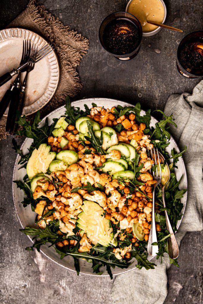 Gerösteter Blumenkohlsalat mit Kichererbsen, Avocado, Gurke, Feta, Rauke und Honig-Senf-Dressing #blumenkohl #ofengericht #kichererbsen #vegetarischerezepte #veggie #vegan #salat #kichererbsensalat #blumenkohlsalat
